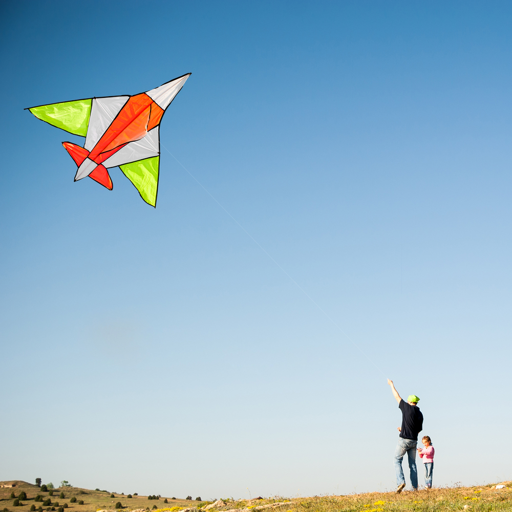 Kite flying in blue sky with kid on the ground