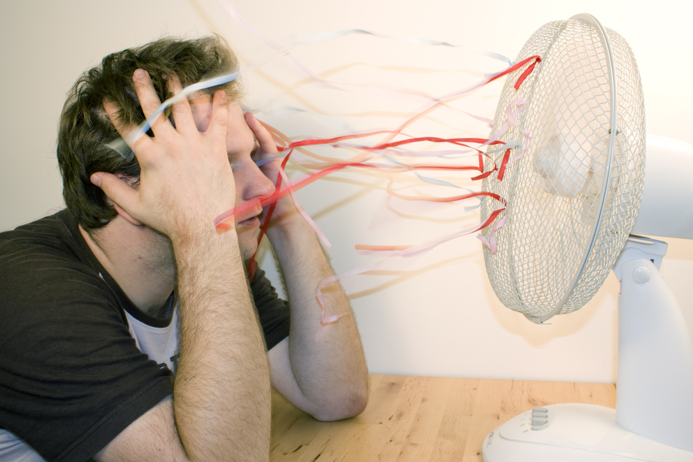 Man in front of fan needs A/C in his office.