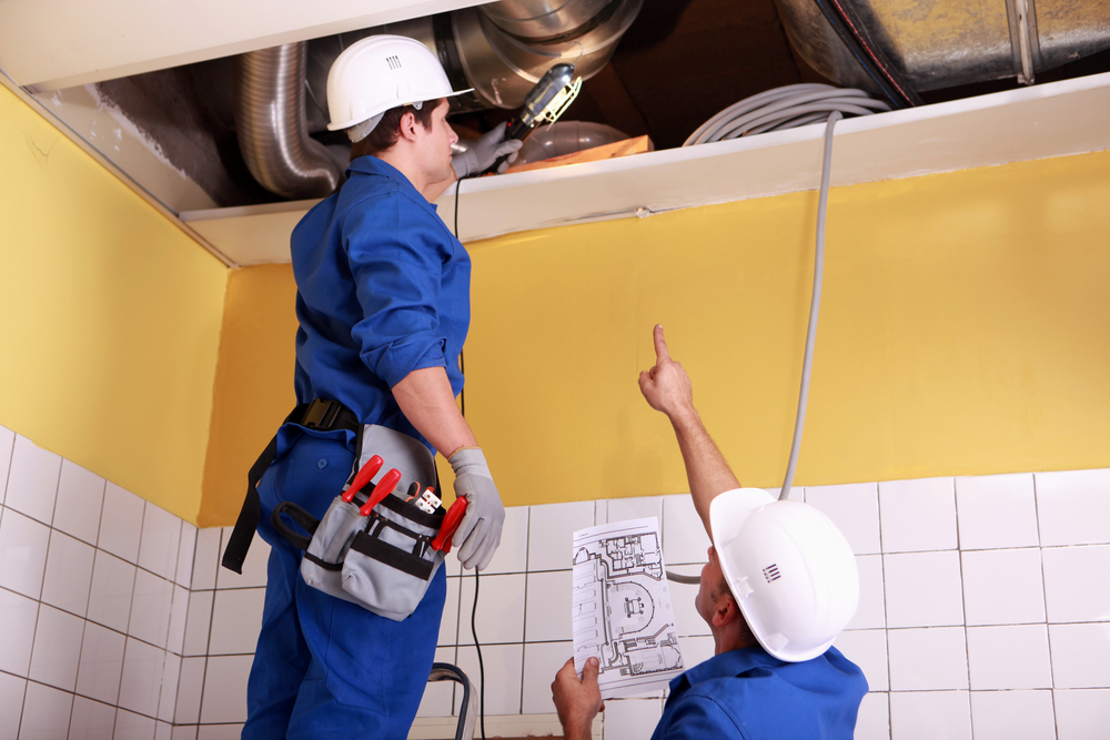 Air duct cleaners in blue uniforms inspecting air ducts